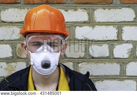 The Guy Is A Construction Worker In A Protective Construction Helmet A Respirator And Protective Gla
