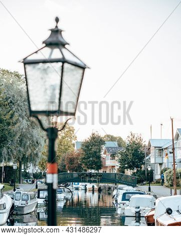 Small Town Canal With Small Boats And A Lamp