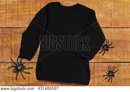 Black Long Sleeve T-shirt Mockup. Black T-shirt On Orange-brown Wooden Background With Spiders. T-sh