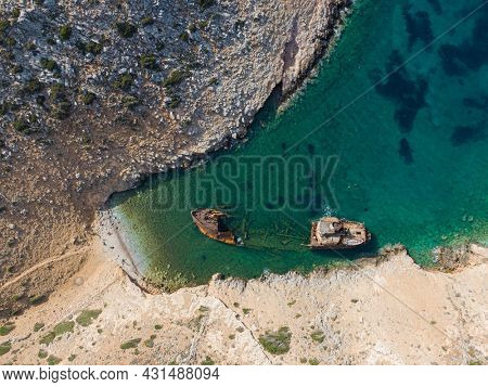 aerial drone view of Shipwreck Olympia boat in Amorgos island during summer holidays, at the coastal rocky area, people on the beach, Cyclades, Greece. Travel background
