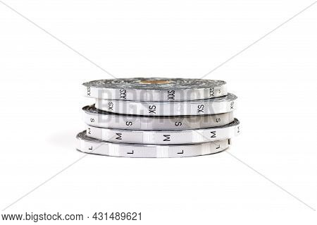 Close-up Of Size Tag Rolls Tape Measures. Silver Coils Lying On Top Of Each Other With Size Tags And