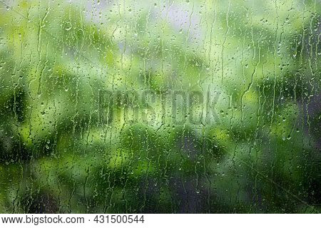 Close Up On Flowing Water Of Raindrop On Glass Window With Blurry Background Of Green Tree.