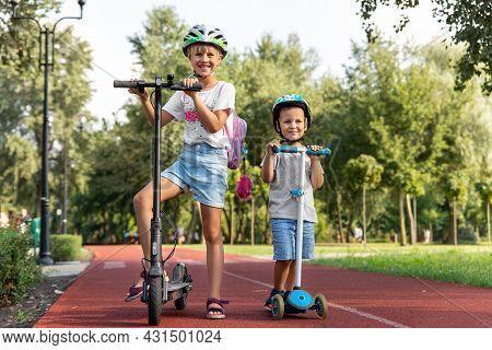 Portrait Of Two Cute Blond Little Caucasian Sibling Kids Girl Wear Safety Helmet Enjoy Having Fun Ri