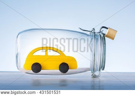 Yellow Toy Car Protected In Glass Safe With Lock On Blue Background. Car Insurance Concept. Safety O