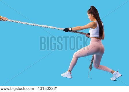Strong Muscled Woman Posing With The Sport Rope And Making Exercises With Pulling The Rope Towards H