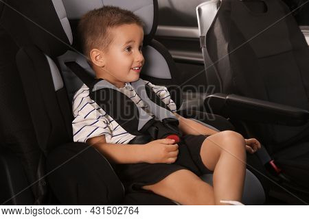Little Boy Fastened With Car Safety Belt In Child Seat