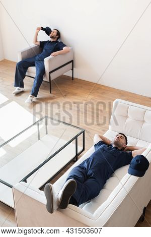 High Angle View Of Movers Resting In Modern Living Room