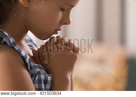 Cute Little Girl With Hands Clasped Together Praying On Blurred Background, Closeup. Space For Text