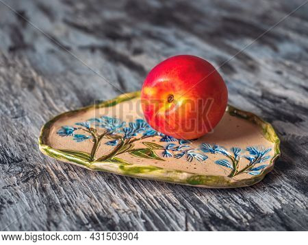 Ripe Nectarine On A Decorative Plate With A Pattern