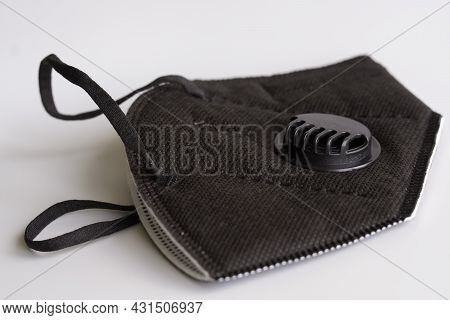 Black Respirator With A Filter And A Valve Lies On A White Background. The Respirator Has A Kn95 Pro