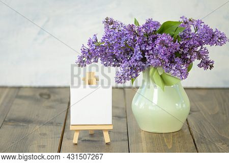 Lilac Flowers. Spring Or Summer Background With Lilac Branches In A Clay Vase, Empty Molbert On A Wo