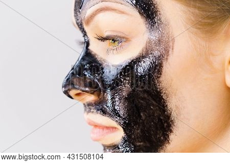 Woman Applying Black Cleanser Mask To Face