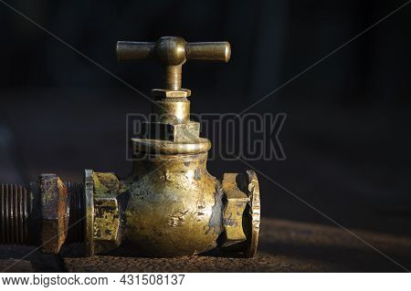 Vintage Old Brass Water Tap Isolated On A Dark Background. Tap Valve. Old Copper Retro Faucet On A R
