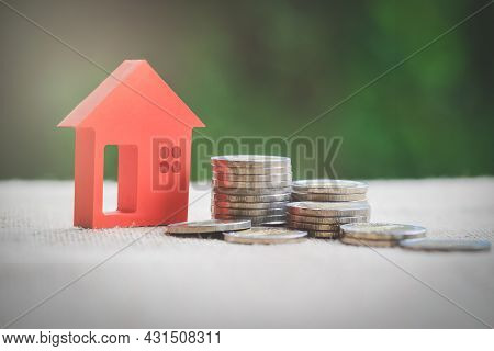 Red House And Pile Of Coins. Natural Background. Financial Strategy Ideas For Real Estate Investment
