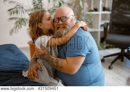 Little Girl Hugs And Kisses Smiling Bearded Plump Father Sitting On Bed At Home