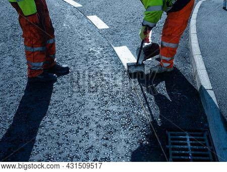 Roadworker Applying Thermoplastic Road Marking On The Freshly Laid Tarmac During New Roundabout And