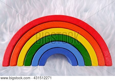 Wooden Colorful Toy Rainbow On A White Fur Background,similar To An Imitation Of A Cloud.montessori