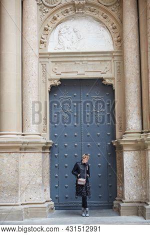 Montserrat, Spain - April 5, 2019: Young Wonan Poses In Front Of The Santa Maria De Montserrat Abbey