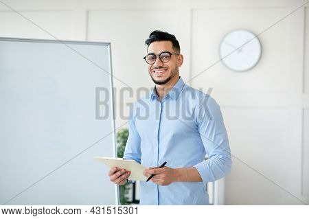 Arab Male Teacher Standing Near Empty Blackboard, Giving Remote Lecture On Web, Speaking To Students