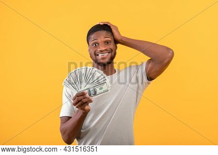 Big Luck And Profit. Shocked Black Man Holding Lots Of Money, Cannot Believe His Big Win Over Yellow