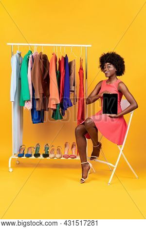 Black Shopaholic Woman Showing Digital Tablet Screen On Yellow Background
