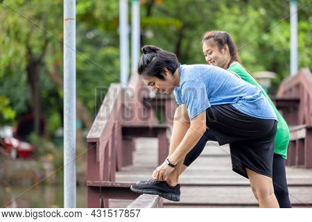 A Fitness Couple Stretches In The Park. In The Morning, A Young Man And A Young Woman Exercise Toget