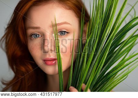Ginger-haired Young Female Looking At Camera Through Plant, Gray Background