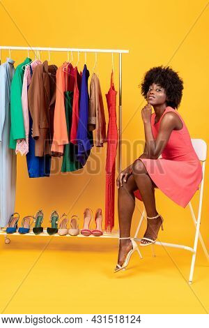 Black Female Shopaholic Posing Sitting Near Clothing Rack, Studio Shot