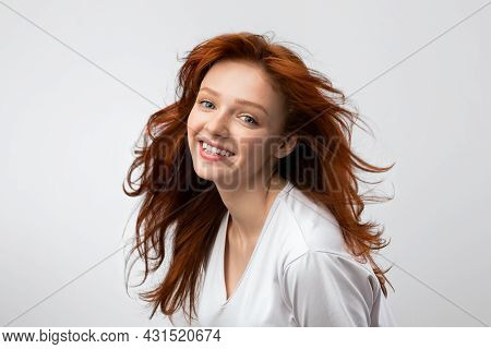Headshot Of Smiling Red-haired Young Female Over Gray Background
