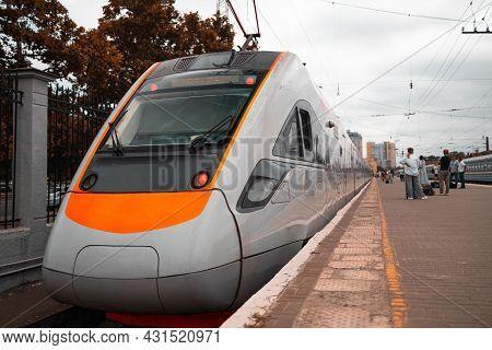 High Speed Orange Train At The Train Station At Sunset. Modern Intercity Passenger Train On A Railwa