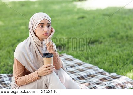 Pensive Attractive Millennial Arabian Female In Hijab With Cup Of Drink Takeaway
