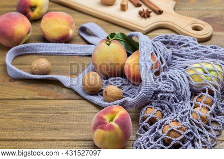Peaches With Green Leaves In Fabric Mesh Bag. Walnuts, Cinnamon Sticks And Star Anise On Board. Wood
