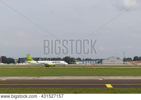 There Is An Airbaltic Plane On The Runway Of Riga Airport. Riga International Airport, Marupe, Latvi