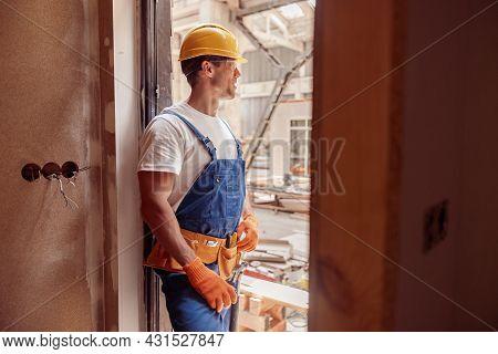 Athletic Male Builder In Work Overalls Standing In Doorway