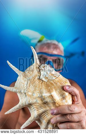 Man In Snorkeling Gear With Mask And Snorkel Is Showing A Shell