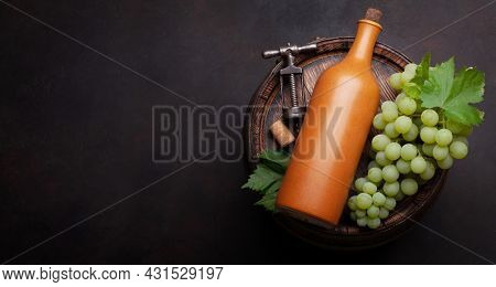 White grape, vintage corkscrew and wine bottle on old wooden wine barrel. Top view flat lay with copy space