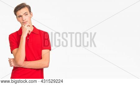Portrait of thoughtful young man looking up isolated over white background. Photo of  pensive white guy in a red shirt.  Male person is thinking. Person is thinking looking away.