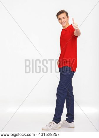 Full Portrait of happy young man showing thumbs up gesture, isolated over white background. Photo of smiling  Handsome white guy in a red shirt with big thumb up. Positive Male person shows big thumb