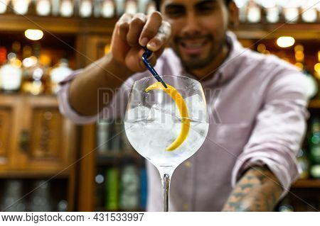 Bartender Decorating Glass Of Fresh Alcoholic Cocktail On Bar Counter, Close-up.