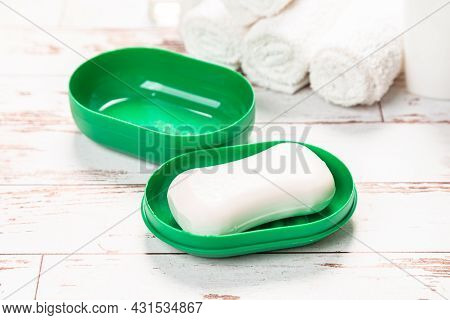 New Soap On A Green Plastic Soap Dish, On A White Wooden Background.