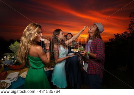 Group of friends having ?furshet in the backyard at summer sunset. Young woman quietly is feeding her boyfriend