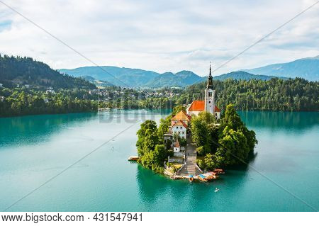 Aerial View Of Lake Bled With Assumption Of Mary Pilgrimage Church On The Small Island On The Backgr
