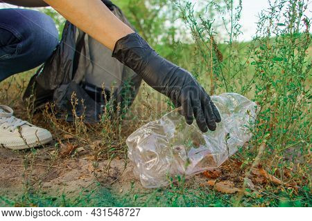 Young Woman Volunteer Collects Trash In Trash Bag Rubbish In Nature. Environment And Plastic Waste.