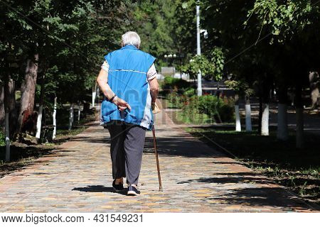 Old Woman Walking With A Cane On A Street In Town Park. Limping Person, Diseases Of The Spine, Elder