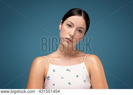 Natural Young Beautiful Woman With Freckles On Face. No Makeup. Blue Pastel Studio Background.