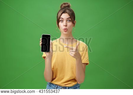 Portrait Of Intrigued Woman Cannot Wait Use New Smartphone Holding Phone And Pointing At Cellphone S