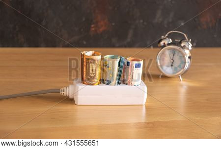 Different Euro Bills With 50, 20 And 10 Euro Bills Placed In The Sockets Of A Power Strip And A Cloc