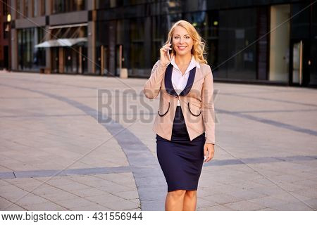 Happy Businesswoman In Suit Talks By Phone Near Business Center.