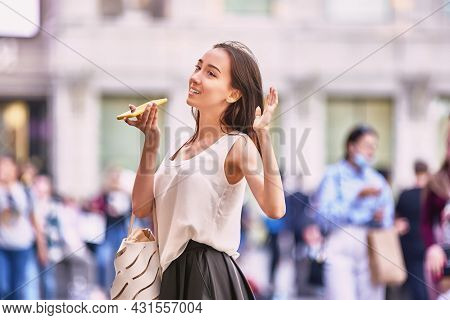 Slender Woman Is Talking By Phone On Crowded Street.