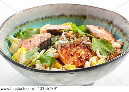 Asian traditional dish - fried rice with egg, vegetables, and salmon. Pan asian wok with rice, egg and fish on white background. Nasi goreng with salmon on isolated background with shadows